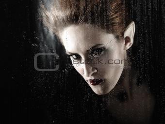 beautiful fashion vampire woman behind rainy window