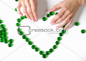 Beautiful hands building a heart sighn from green stones