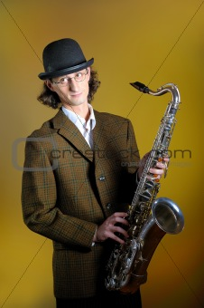 portrait of young funny man in bowler hat holding saxophone.