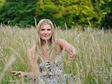 Pretty summer woman on yellow wheat field in countryside