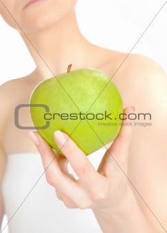 Green apple in a beautiful hand of woman. white background