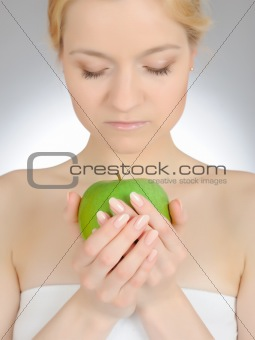 Green apple in a beautiful hand of woman with perfect nail