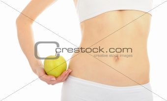 woman with beautiful body holding an apple near the slim waist.