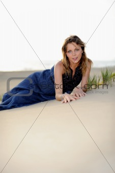 Beautiful fashion woman sitting on the beach in sand