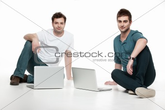 men sitting in front of laptops