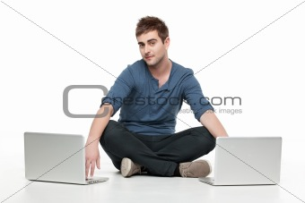 guy sitting behind two laptops