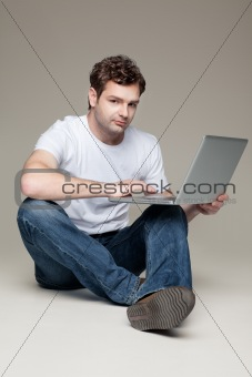man sitting and holding laptop