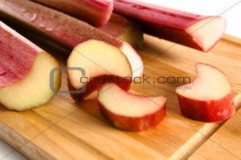 Rhubarb on a kitchen board, it is isolated on white