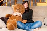 Young woman embracing teddy bear sitting on sofa