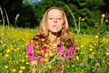 Beautiful woman blows away dandelion
