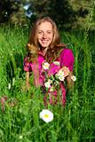 Beautiful smiling woman among the grasses and daisies