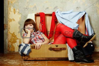 Attractive woman sitting in a suitcase