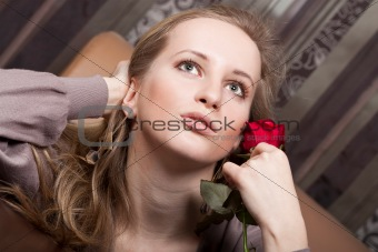 Beautiful young lady with a red rose