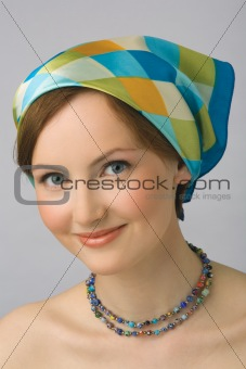 Portrait of the young girl in kerchief and beads