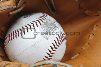 Close up of baseball in catcher's mitt with shallow depth of field
