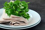 plates with a linen napkin and a sprig of parsley - organic menu