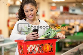 Smiling woman using mobile phone in shopping store