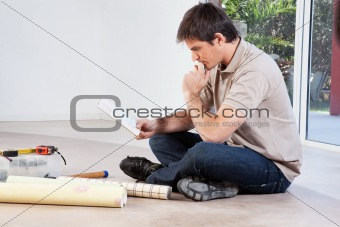 Man sitting on floor and going through color swatch
