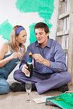 Couple sitting on floor and having champagne