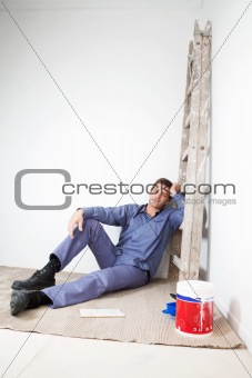 Thoughtful mature man sitting on floor