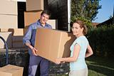 Portrait of couple carrying cardboard box
