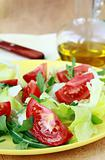 fresh salad with tomato and arugula, olive oil in the background