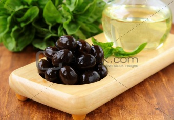 black olives and a bottle of oil on a wooden stand