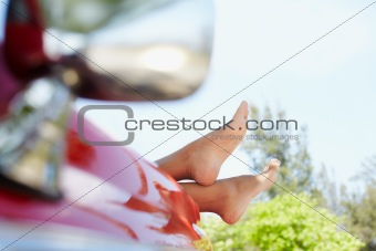 woman lying in cabriolet car with feet out of window