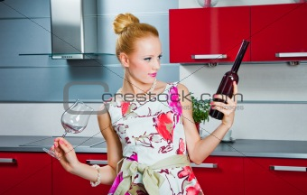 blonde girl with glass and bottle of wine in interior of red kitchen