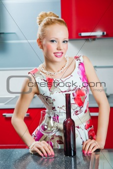 girl with glass and bottle of wine in interior of red kitchen