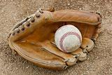 An old worn baseball in a baseball glove