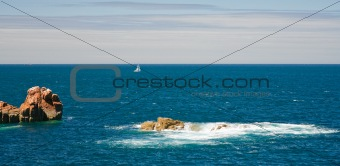 view on sea with pink rocks and yacht