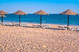 straw beach umbrellas on ocean coast