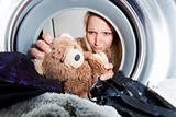 young woman picking a teddy bear from a washing machine