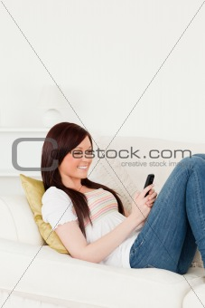 Good looking red-haired woman writing a text on her phone while