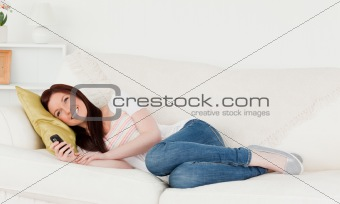 Pretty red-haired woman writing a text on her phone while lying