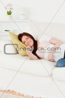 Pretty red-haired woman watching tv while lying on a sofa