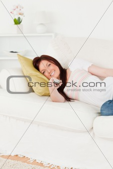 Cute red-haired woman watching tv while lying on a sofa
