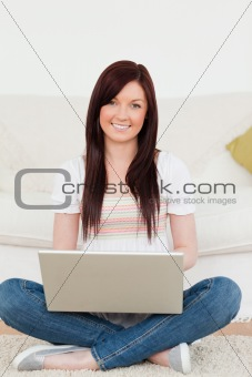 Attractive woman relaxing with her laptop while siting on a carp