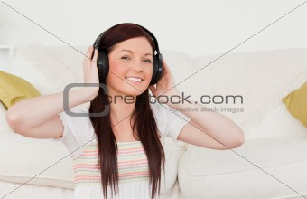 Beautiful red-haired woman listening to music with headphones wh