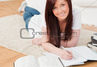 Attractive red-haired girl studying for while lying on a carpet