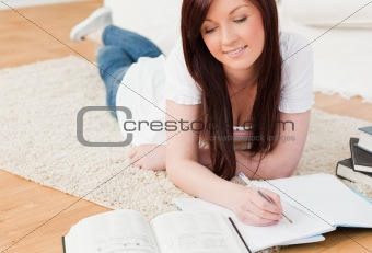 Beautiful red-haired girl studying for while lying on a carpet