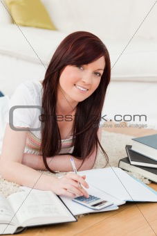 Attractive red-haired female studying for while lying on a carpe