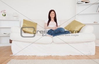 Beautiful red-haired woman posing while sitting on a sofa