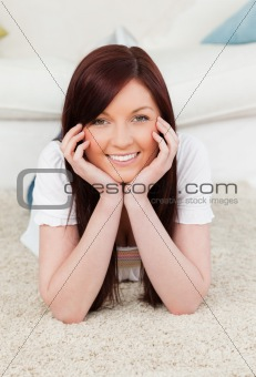 Attractive red-haired female posing while lying on a carpet