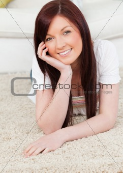 Beautiful red-haired female posing while lying on a carpet