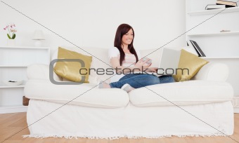 Attractive female sitting on a sofa is going to make a payment o