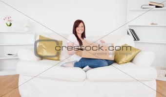 Beautiful red-haired female opening a carboard box while sitting