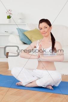 Cute woman doing yoga on a gym carpet