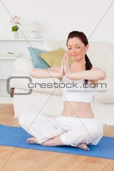 Attractive female doing yoga on a gym carpet